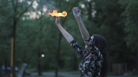 kmenový : Grace beautiful girl performing a show with flame standing in front of forest. Skillful fireshow artist exhaling powerful fiery jet. Slow motion. Female breathes out large stream of fire