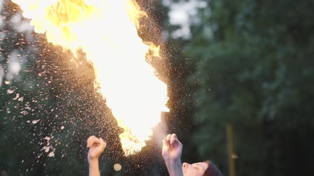 kmenový : Cute young grace girl performing a show with flame standing in front of forest. Skillful fireshow artist exhaling powerful fiery jet. Slow motion. Female breathes out large stream of fire