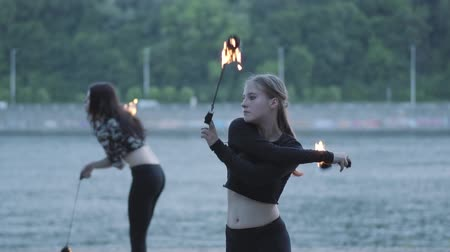 skillful : Two young women performing a show with flame balls standing on the riverbank. Skillful fireshow artists showing mastery of motion of fire. Slow motion Stock Footage