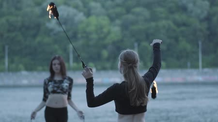 ustalık : Two young women performing a show with flame balls standing on the riverbank. Skillful fireshow artists showing mastery of motion of fire. Slow motion Stok Video