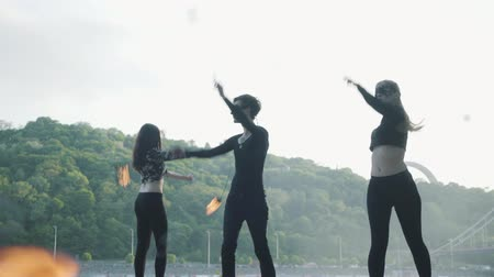 zauberer : Young slim man and two beautiful women simultaneously perform show with flame while standing in front of road and woods. Skillful fireshow artists showing mastery of motion of fire in the evening