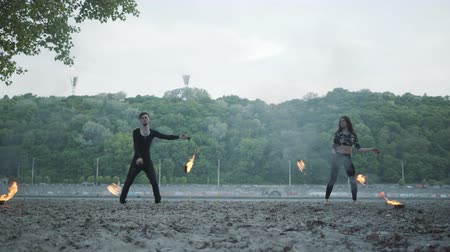 племенной : Young beautiful girl and handsome man in black clothes performing show with flame standing on the riverbank. The woman golding fireball while man exhaling powerful fiery jet over her head. Slow motion