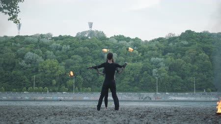 head over : Young beautiful girl and handsome man in black clothes performing show with flame standing on the riverbank. The woman golding fireball while man exhaling powerful fiery jet over her head. Slow motion