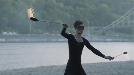 uzak : Young slim man in black clothes and mask performing a show with flame standing on riverbank. Skillful fireshow artist showing mastery of motion of fire outdoors Stok Video
