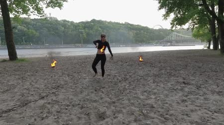 ustalık : Confident slim woman dancing, performing a show with fireball standing on sand. Skillful fireshow artist showing mastery of motion of fire and graceful passionate dance. Top view, drone shooting