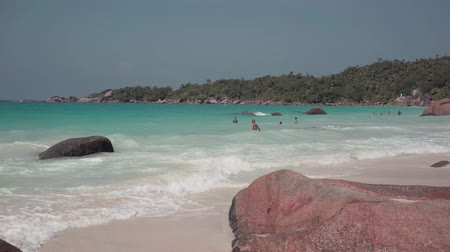 tropy : Seychelles. Praslin Island. The beach of an elite resort on an island in the Indian Ocean. Tropical island luxury vacation. People bathe and sunbathe on vacation.