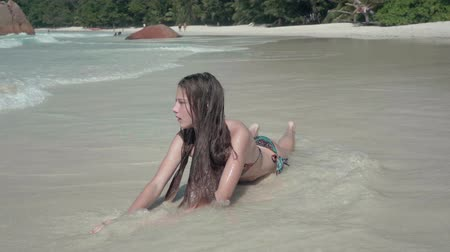 praslin : Seychelles. Praslin Island. Attractive girl relaxing in the clean water on the sand. The lady resting on the islands. Clean waves roll on the beach. Tourism, relax, vacation, travel