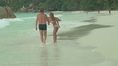 praslin : Seychelles. Praslin Island. Beautiful happy couple resting on the beach on island. Pretty woman in striped swimwear taking the hand of her husband. The man and woman on the sandy beach. Tourism, relax, vacation, travel concept
