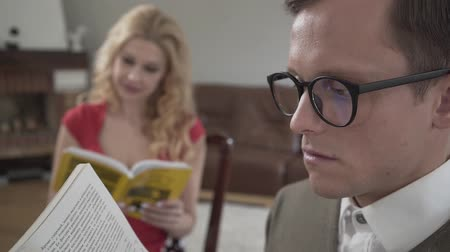 pateta : Young modestly dressed man in glasses reading the book in the foreground while curly blond woman reading the magazine on the background. The nerd and hot woman