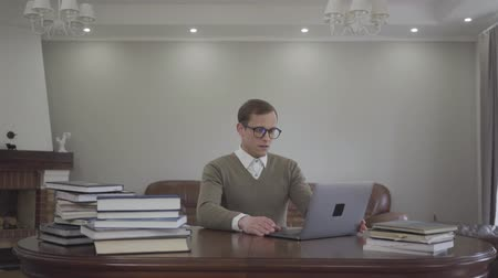 acadêmico : Young modestly dressed man in glasses sitting at the wooden table in the office, many books are on the table. Handsome nerd opening the laptop and start working