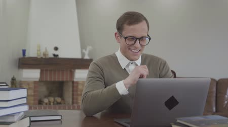 получать : Portrait smiling modestly dressed man in glasses sitting at the wooden table at home, many books are on the table. The nerd working on his laptop and has good news