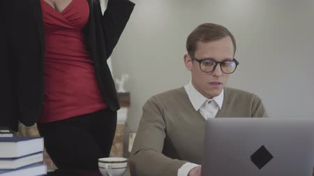 совращение : Portrait young modestly dressed man in glasses sitting at table at home, working on laptop. Beautiful woman with a deep neckline bends over and offers him coffee, a man is confused. Cute nerd and hot secretary