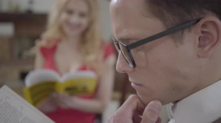 pateta : Close-up of young concentrated man in glasses reading the book in the foreground while pretty blond woman looking at him smiling on the background. The hot woman flirting with nerd