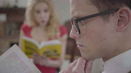 изумление : Close-up of young concentrated man in glasses reading the book in the foreground while pretty blond woman talking to him and smiling on the background. The hot woman flirting with nerd