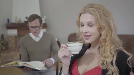 luxúria : Beautiful blond woman drinking coffee in the foreground while modestly dressed man reading the book on the background. The nerd and hot woman doing their things