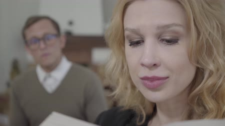 félénk : Closeup face of beautiful blond woman reading aloud the book in the foreground while modestly dressed man looking at the lady on the background. The nerd and hot woman working together Stock mozgókép