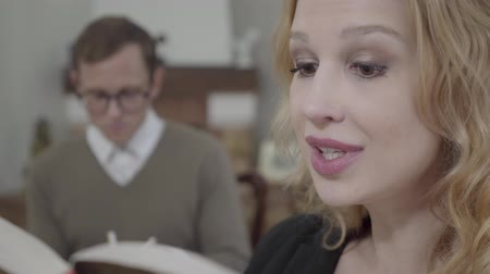 szerény : Close-up face of beautiful blond woman reading aloud the book in the foreground while modestly dressed man looking at the lady on the background. The nerd and hot woman working together