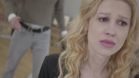gritante : Pretty blond woman in the foreground crying, an emotional angry man yelling and shouting on the background. The couple has a quarrel. Difficulties in relationship