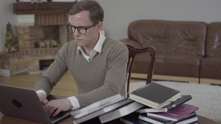 čtenář : Portrait young modestly dressed man in glasses sitting at the wooden table in the office working on his laptop. Unrecognizable angry woman bringing and throwing on the desk stack of books