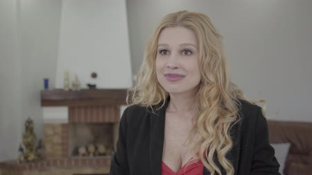 recrutamento : Portrait of adorable blond woman with curly hair in formal wear talking in front of the camera in the room with modern furniture. The lady on interview.