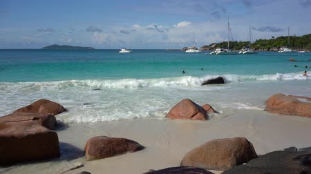 seychely : Seychelles. Praslin Island. Beautiful view of the stony coast of the island located in the Indian Ocean. Private yacht in the blue sea water on the background. People bathe in the sea.