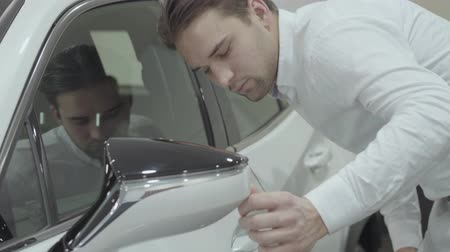 sprzedawca : Successful businessman inspects newly purchased auto from the car dealership. Car showroom. Advertising concept. Wideo