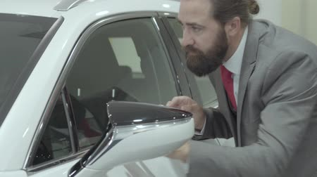 publicity : Portrait cute confident bearded businessman in a business suit inspects newly purchased auto from the car dealership. Car showroom. Advertising concept.