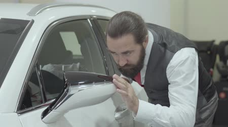 гласность : Portrait attractive confident bearded man in a business suit inspects newly purchased auto from the car dealership. Car showroom. Advertising concept. Стоковые видеозаписи