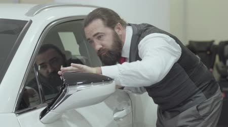 гласность : Portrait attractive cute confident bearded businessman in a business suit inspects newly purchased auto from the car dealership. Car showroom. Advertising concept.