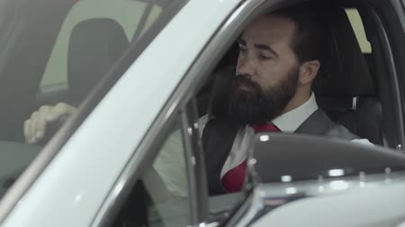 car rental : Portrait successful bearded man sitting in passenger compartment of the new vehicle inspects the interior of the newly purchased auto from the dealership. Car showroom. Advertising concept. Stock Footage