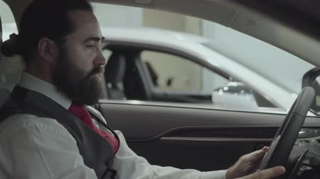 publicidade : Portrait attractive successful bearded businessman sitting in the vehicle and inspects newly purchased auto from the car dealership. Car showroom. Advertising concept.