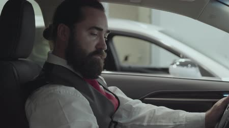 publicidade : Portrait attractive confident bearded businessman sitting in the vehicle and inspects newly purchased auto from the car dealership. Car showroom. Advertising concept.