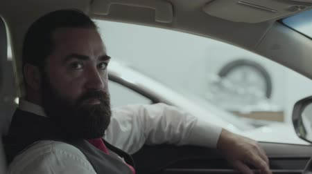 publicity : Portrait attractive confident bearded businessman sitting in the vehicle in the car dealership. Car showroom. Advertising concept. Stock Footage