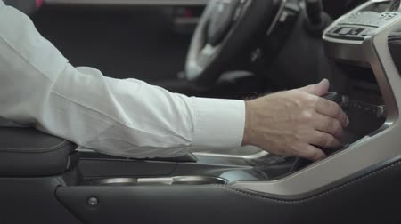 гласность : Unrecognized confident man sitting in the vehicle and inspects newly purchased auto from the car dealership. Car showroom. Advertising concept.