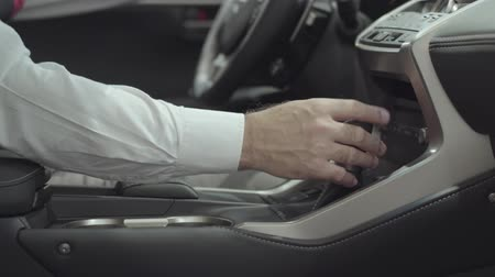гласность : Unrecognized successful man sitting in the vehicle and inspects newly purchased auto from the car dealership. Car showroom. Advertising concept.