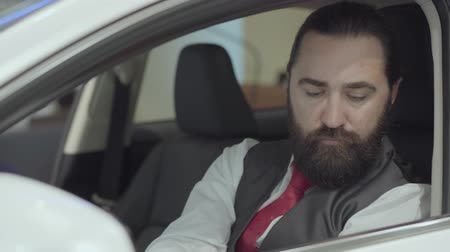 объяснять : Portrait attractive confident bearded man sitting in the vehicle and inspects newly purchased auto from the car dealership. Car showroom. Advertising concept.
