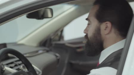sprzedawca : Portrait attractive cute confident bearded businessman sitting in the vehicle and inspects newly purchased auto from the car dealership. Car showroom. Advertising concept. Wideo