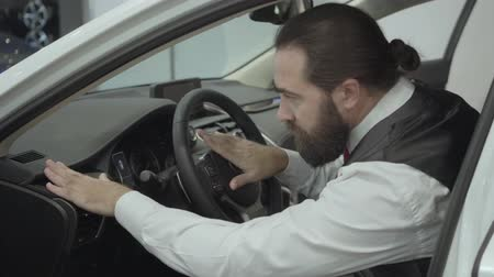 publicity : Portrait attractive confident bearded businessman sitting in the vehicle and inspects newly purchased auto from the car dealership. Car showroom. Advertising concept.