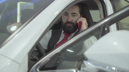 гласность : Portrait attractive confident bearded businessman sitting in the vehicle and inspects newly purchased auto from the car dealership. Successful man talking by cell phone while sitting in a car.