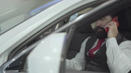 publicité : Portrait attractive confident bearded businessman sitting in the vehicle and inspects newly purchased auto from the car dealership. Successful man talking on the phone while sitting in a car. Vidéos Libres De Droits