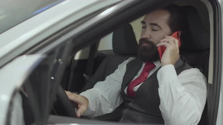 publicity : Portrait attractive confident bearded businessman sitting in the vehicle and inspects newly purchased auto from the car dealership. Successful man talking cell phone while sitting in a car.