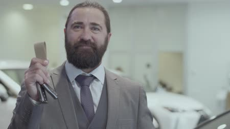 publicity : Portrait of a successful bearded business man in a business suit showing the key of a luxury car looking into the camera. Car showroom. Advertising concept. Stock Footage