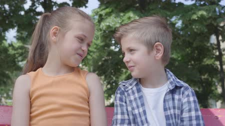 нежный : Portrait of cute blond boy and pretty girl sitting on the swing on the playground. Couple of happy children. Funny kids in love outdoors.