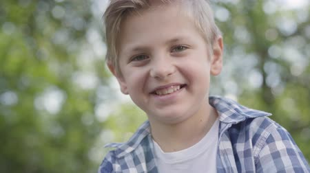 deep learning : Close-up portrait of cute handsome boy in checkered shirt looking into camera sitting in the park. Summertime leisure outdoors. Lovely kid studying under the trees