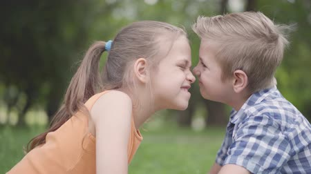 casal : Side view of cute boy and girl sitting in the park, rubbing their noses and having fun. A couple of happy children. Funny carefree kids in love