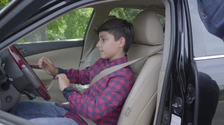 bérlet : Unrecognizable father teaching his son to drive the car. The boy fastens his seatbelt under dads control. The child and father spending time together. A man passes on knowledge to son Stock mozgókép