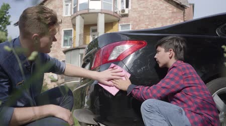 limpar : Young father teaching his son to care about the car. The man and a boy wiping the machine with a rag close-up. A man passes on knowledge to a son, teaching him to be careful with auto