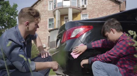 limpar : Cute young father teaching his son to care about the car. The man and a boy wiping the machine with a rag close-up. A man passes on knowledge to a son, teaching him to be careful with auto Vídeos