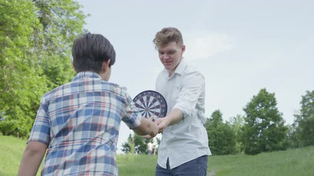 mıknatıs : The young father holding darts while his son throwing darts on a magnet in the circles. Family leisure outdoors. Father and a kid spend time together outdoors. The dad supports his child Stok Video