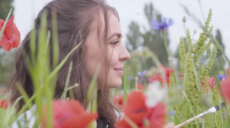 klaprozen : Side view of pretty smiling girl in a poppy field holding a brush for painting close-up. The female artist making masterpiece. Connection with nature. Green and red harmony Stockvideo
